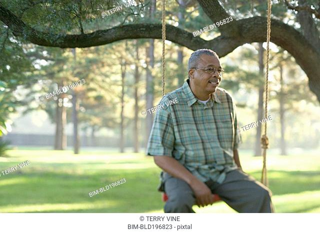 African American man sitting on swing
