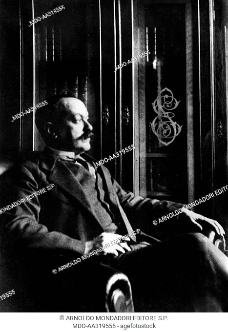 Italo Svevo in an armchair. The Italian writer Italo Svevo sitting in an armchair in front of the bookcase decorated with the initials of his real name
