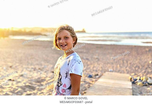 Portrait of smiling blond girl on the beach