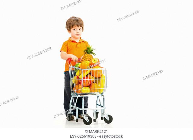 Child shopping. Cheerful little boy carrying shopping cart full of goods and looking at camera while isolated on white