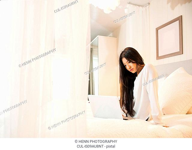 Business woman working on laptop, on bed, in hotel room