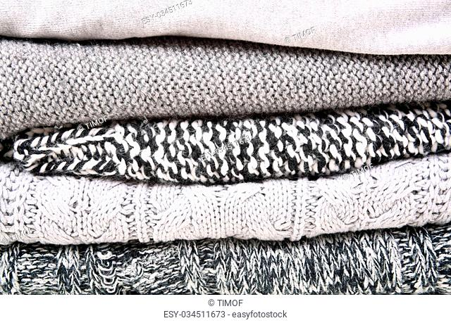 Woolen knitted clothes different texture grey background closeup