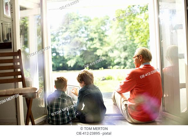 Grandfather and grandsons relaxing in doorway