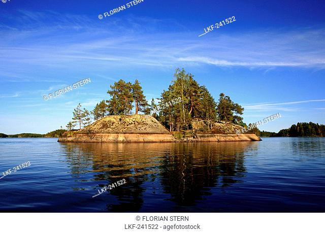 Private island with trees under blue sky, Saimaa Lake District, Finland, Europe