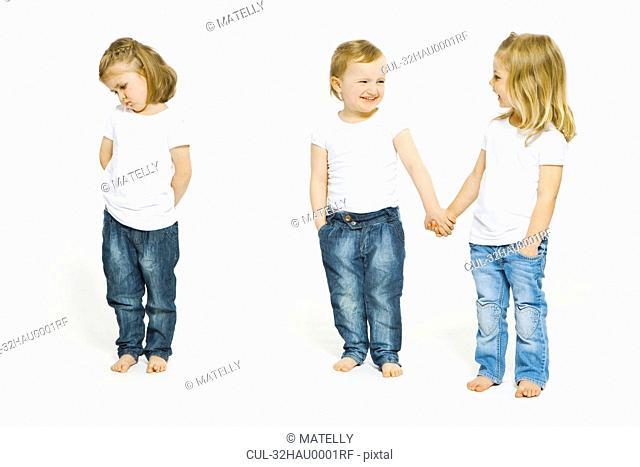 Two girls holding hands, third upset