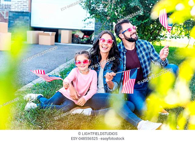 beautiful family with american flags and sunglasses sitting in garden of new house