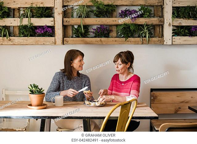 Two Female friends sitting inside a little cafe relaxing. They are buttering a scone and enjoying a coffee