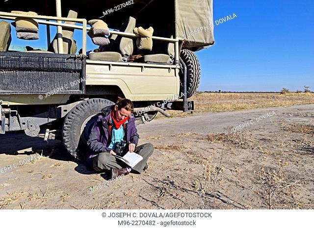 Woman looking at guide book during break in game drive, Savuti, Botswana, Africa