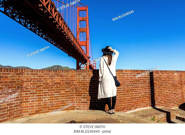 Caucasian woman admiring Golden Gate Bridge, San Francisco, California, United States