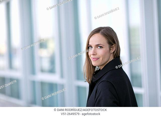 Pretty woman in winter smiling at camera outdoors