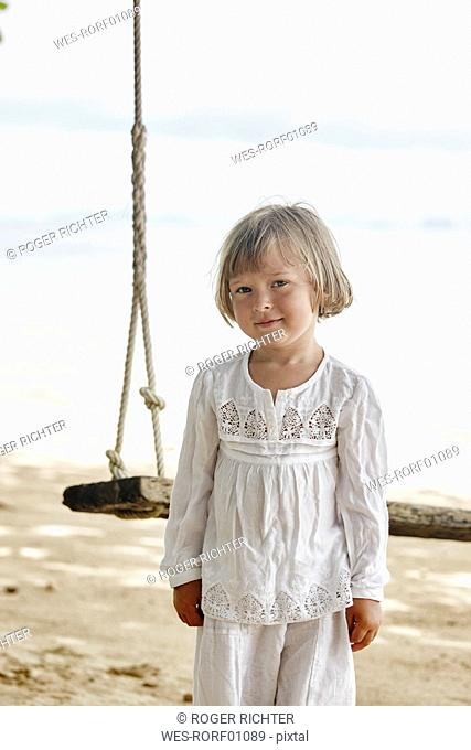 Thailand, Ko Yao Noi, portrait of little girl at a swing on the beach