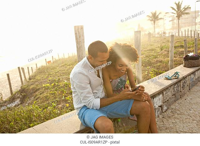 Couple reading smartphone texts at beach, Rio De Janeiro, Brazil