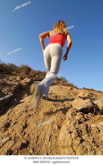 Woman running up rocky trail