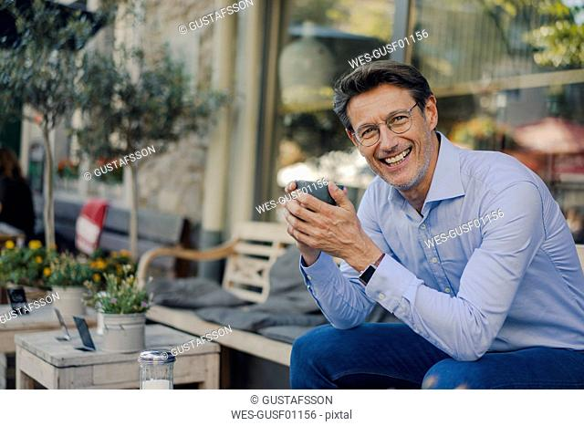 Mature businessman sitting in coffee shop, drinking coffee