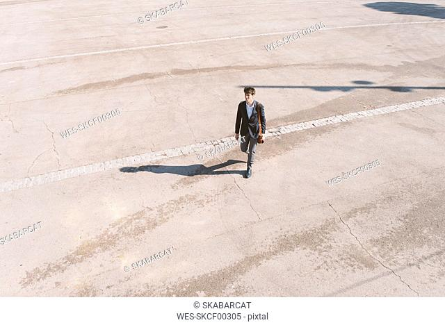 Young man in suit walking