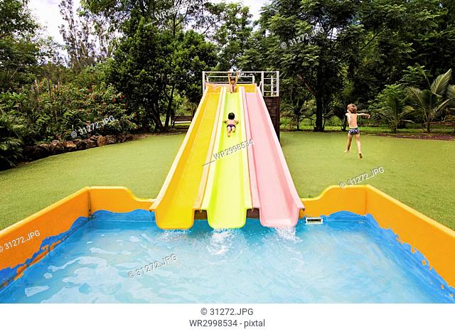 A large shallow paddling pool with three coloured slides into the water, and three children playing, one jumping and running across a garden