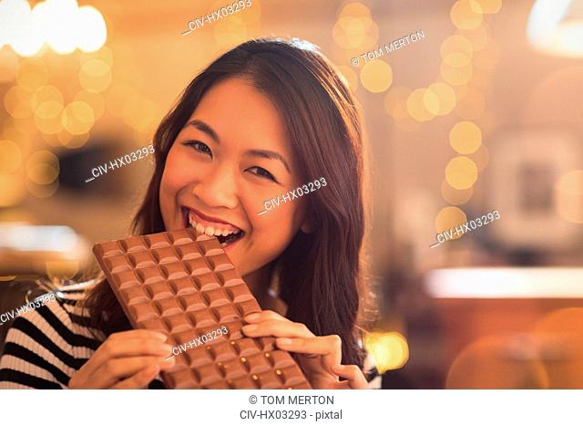 Portrait Chinese woman with sweet tooth craving biting into large chocolate bar