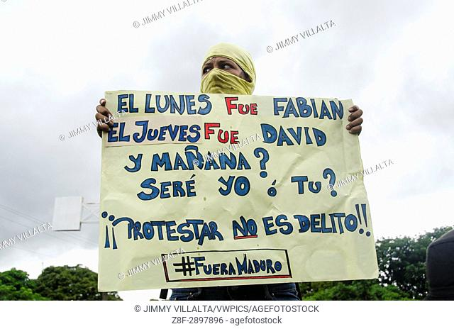 A protester carries a sign that says: Monday was Fabian on Thursday was David, and tomorrow? It will be me or you. Protest is not a crime