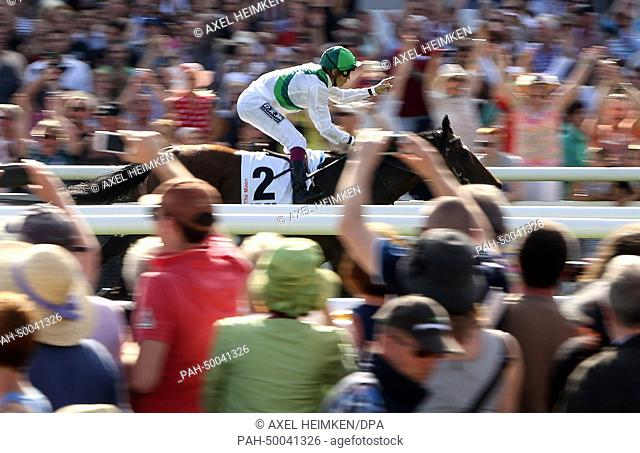 Jockey Christophe Soumillon gestures as he races on his horse 'Sea the Moon' during the German Derby in Hamburg, Germany, 6 July 2014