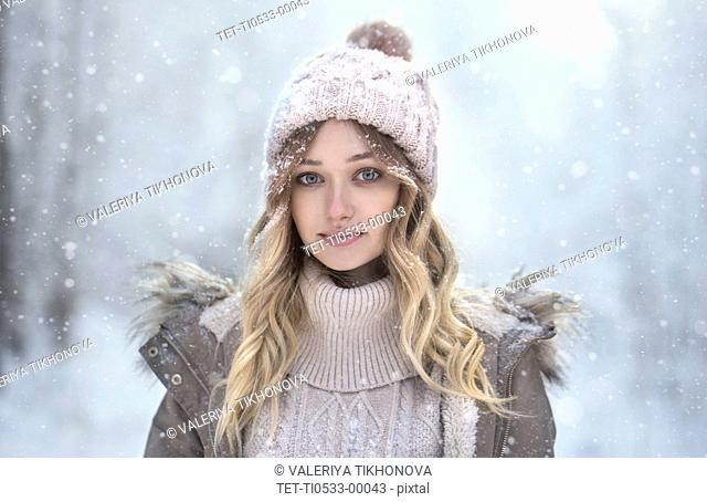 Portrait of young woman in woolly hat under snowfall