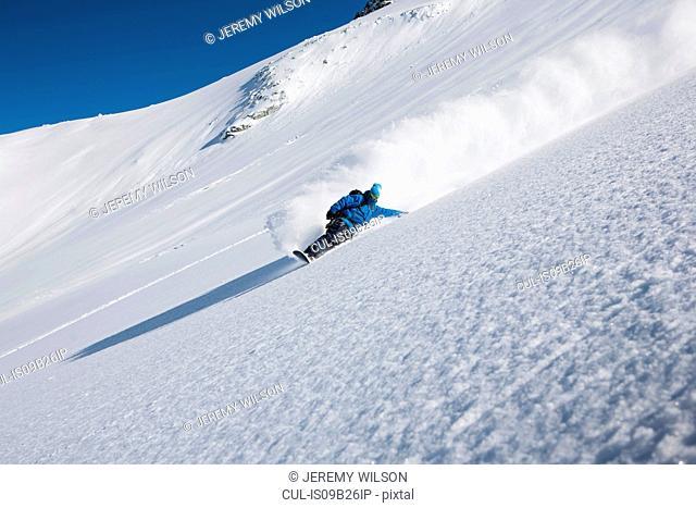 Male snowboarder speeding down steep mountain, Trient, Swiss Alps, Switzerland