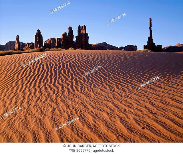 USA, Arizona, Navajo Tribal Park, Sunrise defines texture of sand dunes with rock towers called Yei-Bi-Chei rising in the distance