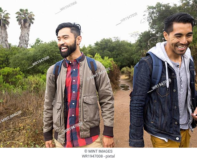 Two smiling young men walking in a park
