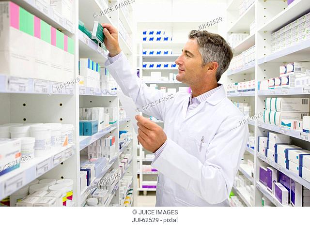 Pharmacist searching for medication on pharmacy shelves