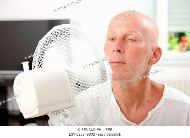 mature man refreshed with a fan in his home