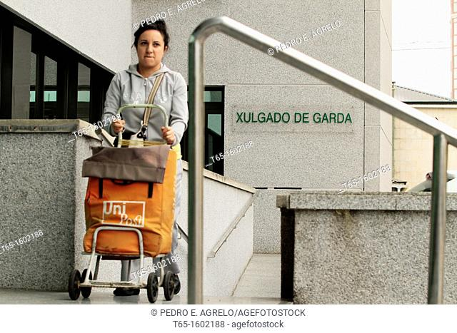 A woman carries mailman documentation to the police court of Lugo