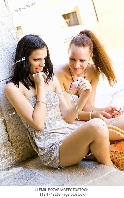 Two girfriends are reviewing digital pictures on a photo camera