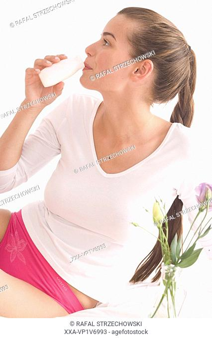 young woman drinking youghurt