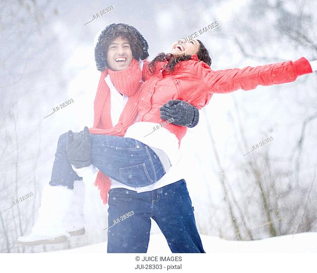 Young man carrying young woman on winter day