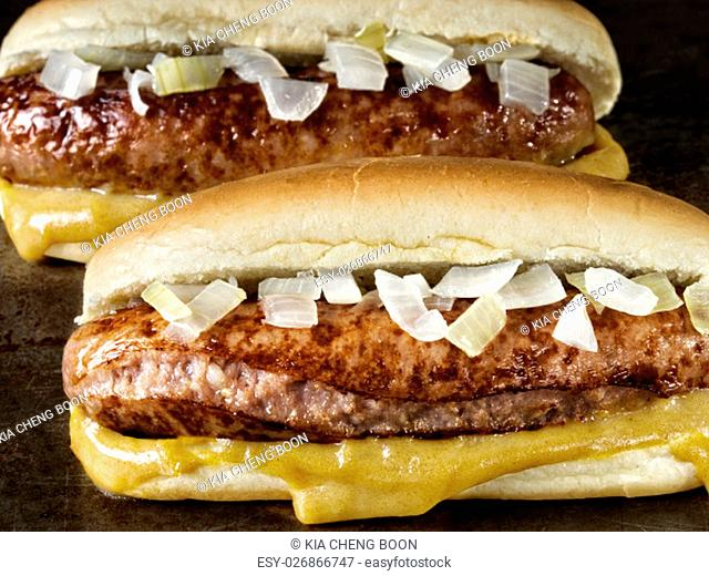 close up of rustic american hot dog with mustard and onion