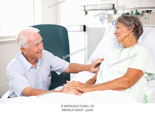 Husband comforting wife in hospital bed