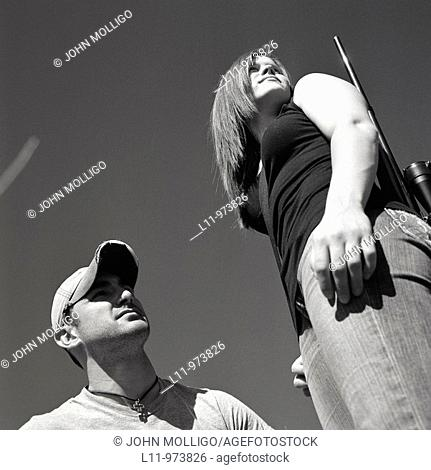 Man and woman with rifle, looking right