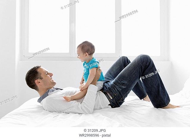 Smiling man lying on his back on a bed, baby boy sitting on his stomach