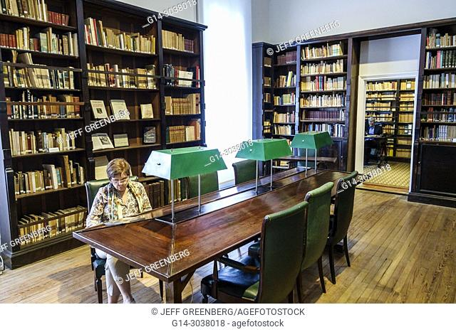 Argentina, Buenos Aires, Belgrano, Museum of Spanish Art Museo de Arte Espanol Enrique Larreta, interior, library, reading table, books, bookshelf, woman