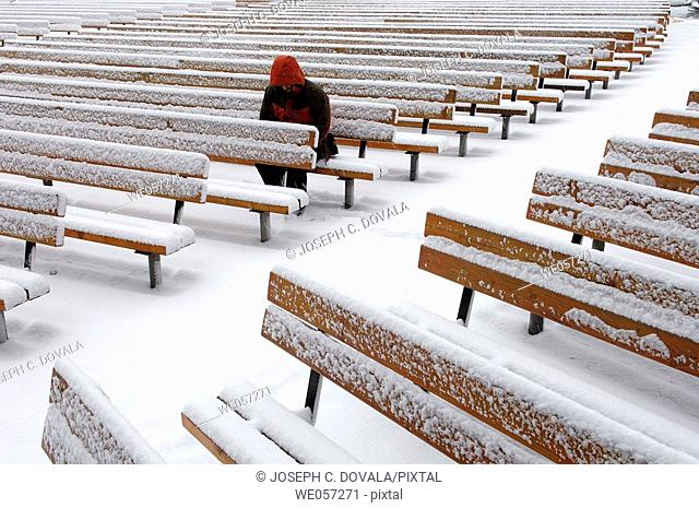 Man sitting alone in outdoor arena during snow storm
