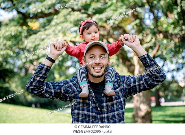 USA, New York, Father with baby girl on his shoulders walking through Central Park