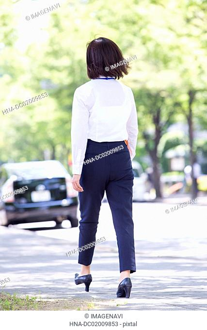 Business woman walking along with tree-lined road