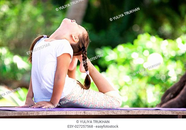 Child doing exercise on wooden platform outdoors. Healthy lifestyle. Yoga girl