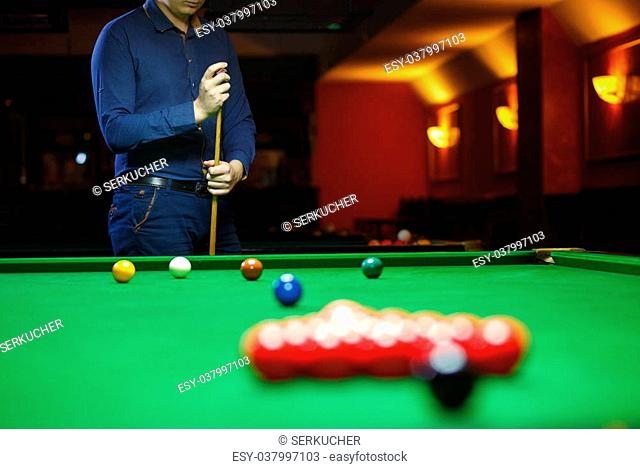 A young man lines up his shot as he breaks the balls for the start of a game of snooker