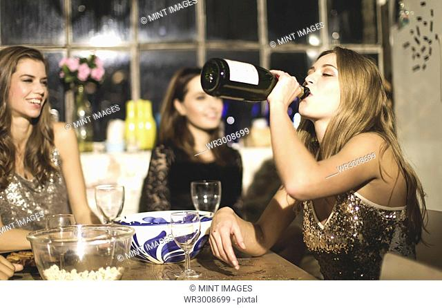 A group of friends around a table at a party, one girl drinking from a bottle of champagne