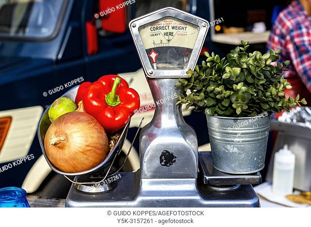 Tilburg, Netherlands. Decorative setup of a plant, some fruits and vegetables on a weight-scale during the annual food truck festival