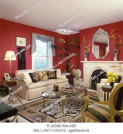 LIVING ROOMS - Classic and traditional look, dark red walls, fireplace and mantle, large ornate Venetian glas mirror. Glass coffee table, with brass legs