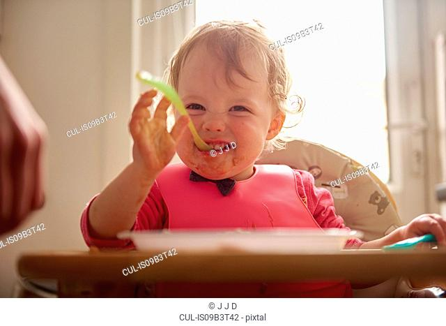 Toddler sitting in highchair, eating meal