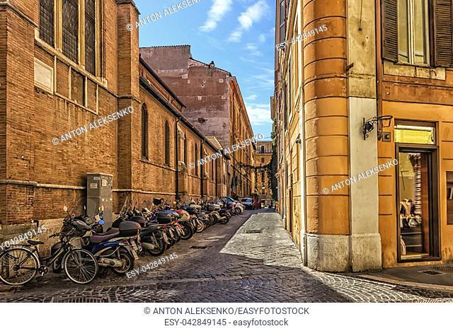 Scooters near the basilica wall in the narrow italian street