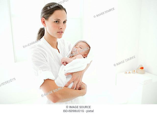 Mother and baby son wrapped in towel