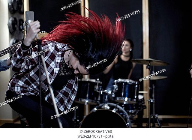 Rock singer shaking her hair at recording studio